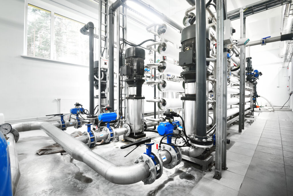 Large industrial water treatment and boiler room. Shiny steel metal pipes and blue pupms and valves.