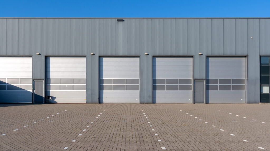 Row of grey industrial Units with roller shutter doors.
